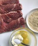 Части лож мяса на разделочной доске Рядом с контейнером ингридиенты для бэттера: майонез, яичко и соль Стоковые Изображения