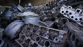 Части металла старых сломанных автомобилей лежат в кучах металлолома в большом ангаре, старых горбах и двигателях сток-видео