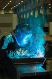 Части металла сварок сварщика в защитном костюме Стоковое Фото