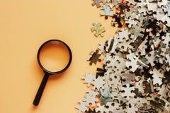 Части мозаики с лупой на бежевом bac цвета Стоковые Фото