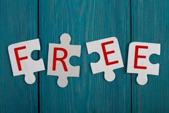 Части мозаики с текстом & x22; FREE& x22; на голубой деревянной предпосылке стоковые изображения rf