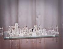 Части на доске. Комплект шахмат вычисляет на играя доске. Стеклянный шахмат Стоковые Изображения
