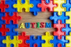Части от красочной мозаики аранжировали сформировать страницу на деревянной предпосылке Барьеры пролома совместно для аутизма стоковые фотографии rf
