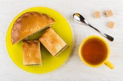 Части пирога с капустой в плите, чае, чайной ложке, сахаре Стоковое Изображение RF