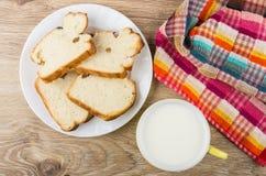 Части плюшки с изюминкой в плите, салфетке и молоке Стоковая Фотография RF