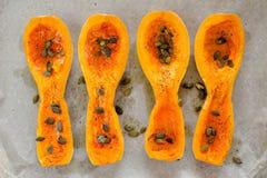 4 части сквоша butternut с семенами тыквы на белой бумаге Стоковое Изображение RF