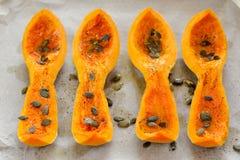 4 части сквоша butternut с семенами тыквы на белой бумаге Стоковая Фотография RF