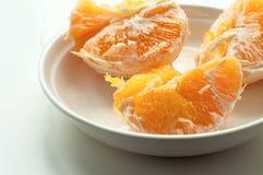 Части сочного апельсина в белой плите Стоковые Фото
