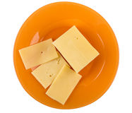 Части сыра в оранжевой плите изолированной на белой предпосылке Стоковые Фото