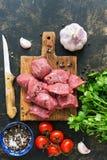 Части сырцового мяса говядины с специями и томатами вишни на темной предпосылке Взгляд сверху, плоское положение стоковое изображение rf