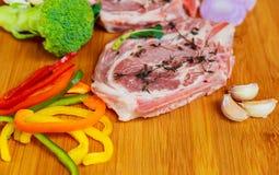 2 части сырцового свинины на деревянных ингридиентах разделочной доски Стоковое Изображение RF