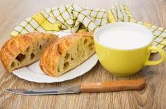 Части сладостной плюшки в плите, салфетке, чашке с молоком Стоковые Изображения