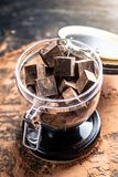 Части темного горького шоколада с какао в стеклянном опарнике на деревянной предпосылке Концепция ингредиентов кондитерскаи стоковое фото