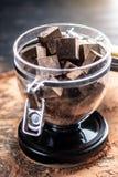 Части темного горького шоколада с какао в стеклянном опарнике на деревянной предпосылке Концепция ингредиентов кондитерскаи стоковые фотографии rf