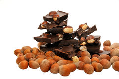 Части темного шоколада с фундуками на белой предпосылке Стоковая Фотография