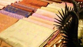 Части ткани шелка на стойле Части мягкой орнаментальной азиатской ткани шелка помещенной на стойле на уличном рынке сток-видео