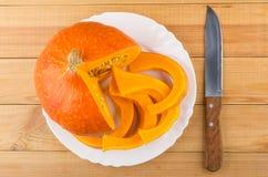Части тыквы отрезка зрелой в белых плите и ноже Стоковое Изображение RF