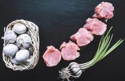 Части филе свинины с чесноком на черной доске намечают стоковое фото rf