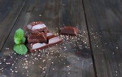 Части шоколада при мята лежа на деревянном Стоковые Изображения RF