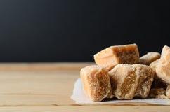 Части Fudge на светлой деревянной таблице с черной предпосылкой Стоковое Фото