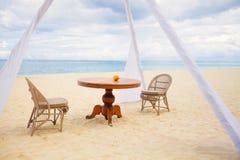Частный обеденный стол и плетеные стулья для романтичного обедающего для пар медового месяца на тропическом пляже Стоковое фото RF