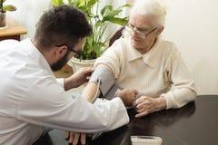 Частный офис ` s доктора Доктор Geriatrician принимает пациента и измеряет ее кровяное давление стоковое фото rf