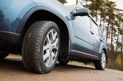 Часть автомобиля крупного плана, колесо на пакостной дороге Стоковое Изображение RF