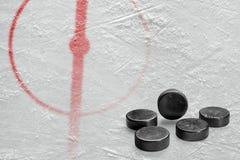 Часть арены хоккея с центральным кругом и шайбами Стоковое фото RF