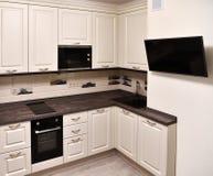 Часть бежевых кухни и ТВ на стене стоковое изображение rf