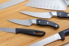 Часть деревянной разделочной доски с различными кухонными ножами Стоковое Изображение RF