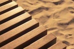 Часть деревянной скамьи против предпосылки песка Стоковые Изображения