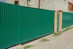 Часть железной зеленой загородки и закрытых стробов на улице около дороги Стоковые Фото