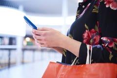 Часть женщины используя мобильный телефон во время покупок стоковое фото
