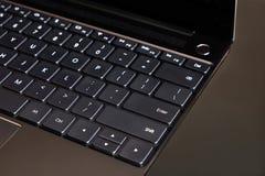 Часть клавиатуры компьтер-книжки и сенсорная панель раскрытой компьтер-книжки на сером взгляд сверху предпосылки стоковое фото rf