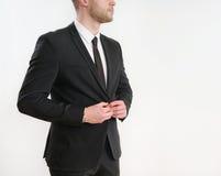 Часть кнопки стороны тела бизнесмена вверх по его черному костюму на белизне Стоковое Изображение
