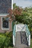 Часть коричневого дома около малого белого моста с зелеными деревьями вокруг его Стоковые Изображения RF