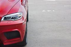 Часть красного автомобиля на предпосылке асфальта стоковое фото rf