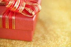 Часть красной подарочной коробки на предпосылке золота яркого блеска Стоковое Изображение