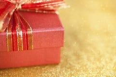 Часть красной подарочной коробки на предпосылке золота яркого блеска Стоковые Изображения RF