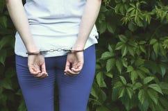 Часть молодого уголовного тела ` s девушки с руками в наручниках против зеленого blossoming плюща выходит предпосылка Концепция  стоковое фото
