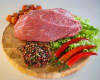 Часть незрелого мяса свинины на деревянной круглой доске на белой предпосылке Стоковые Фото