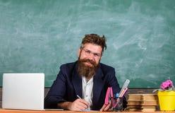 Часть обработки документов жизни учителей Школьный учитель проверяя учителя домашней работы или испытания сидит стол с компьтер-к стоковые фотографии rf
