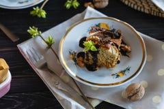 Часть пирога банана на темной деревянной предпосылке Украшенный с зелеными листьями и ветвями весны Стоковые Изображения