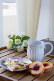 Часть пирога на белой плите, белой кружки персика с чаем Стоковая Фотография