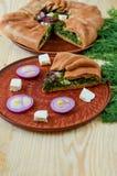 Часть пирога шпината с сыром фета, луком на плите коричневого цвета глины с космосом бесплатной копии Украшенный с свежим укропом Стоковая Фотография
