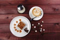 Часть пирожного шоколада и карамелька sauce, чашка капучино на белой плите Взгляд сверху Стоковые Фото