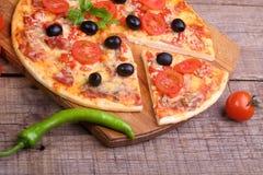 Часть пиццы и пиццы от салями, ветчины и томатов дальше Стоковая Фотография RF