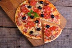 Часть пиццы и пиццы от салями, ветчины и томатов дальше Стоковое Фото
