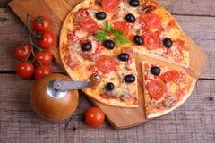 Часть пиццы и пиццы от салями, ветчины и томатов дальше Стоковое Изображение