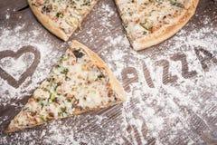 Часть пиццы на коричневой деревянной предпосылке взбрызнутой с мукой Стоковые Изображения RF